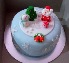 Snowflake themed Christmas cake. On top of the cake you can find small cartoon versions of Santa and a snowman. You can also find a small Christmas tree in the middle completing the design.