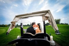 Bride and groom kissing in a golf cart  - wedding pictures