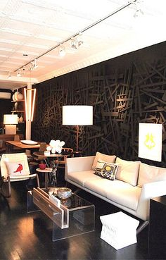 Black plywood strips layered against a black wall painted wall. Looks like 3-D art to me! Gives the wall shadow and  depth. LOVE