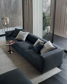 Shangai sofa and pouf with feather padding, removable covering in 14 grafite Hannover fabric, cushions in 14 grafite Hannover and 6 sabbia Norway fabric. Flute coffee table granata glossy lacquered.