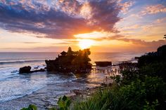 """Tanah Lot means, """"Land in the Sea"""" in the Balinese language. The temple Pura Tanah Lot sits on a large offshore rock that has been shaped continuously over the years by the ocean tide. Tourists throng here during sunset, so for a less distracting visit try to make your pilgrimage during the pre-dawn hours when sunrise views are less crowded but just as rewarding"""