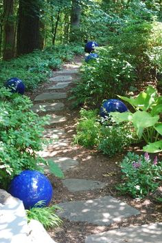You can introduce the concept of rhythm in your garden by repeating certain key elements, as was done with these sculptural ceramic orbs.