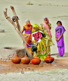 Water shortage . Rural women collecting drinking water from well .