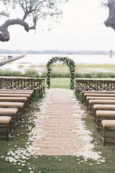 Let the naturally beautiful setting of your venue dictate your ceremony decor and keep things simple with a classic floral arch and linen-upholstered wooden benches. - HarpersBAZAAR.com