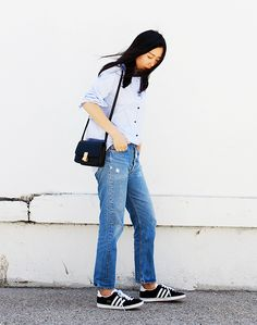 Blogger Andy Heart wears a blue button-down blouse, jeans, Adidas sneakers, and a black box bag