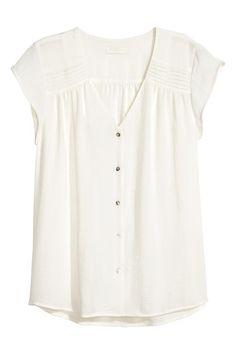 CONSCIOUS. Blusa en crepé vaporoso con pinzas pespunteadas en los hombros, escote de pico, mangas japonesas cortas y botones anacarados delante. Confecciona