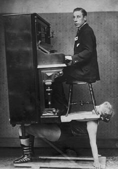 A strongwoman balances a piano and pianist on her chest. (1920)