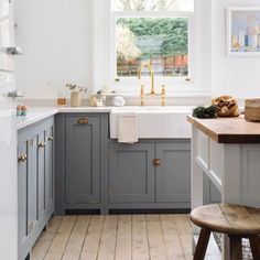 Farmhouse shaker farmhouse kitchen slate grey cabinets, cream counter, brass faucet white apron front sink.