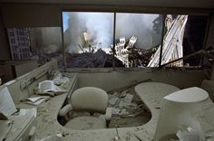 Jonathan Torgovnik made this photograph on 9/12. While it doesn't have a soundtrack, it is an incredibly quiet picture. It forms a bridge between pre and post-9/11—an office that most of us can relate to, have visited, or worked in–against a spectacularly lit backdrop of heinous devastation. 9/11 was the photographic event of all-time; so immense, that it was tough to get grounded in, to take measure of, to begin to believe what had happened. This picture helps.