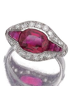 An Art Deco ruby and diamond ring, circa 1930. The oval ruby flanked by calibré-cut similar stones, within a border of brilliant- and circular-cut diamonds.