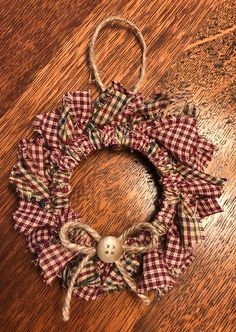 This homespun wreath ornament can be hung on tree or a wall. The colors are navy/green/burgandy/cream and burgandy/cream. 5 inches wide
