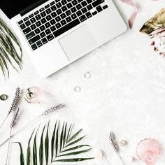 flat lay feminine home office workspace with laptop proteus flower necklace palm branches and accessories. top view