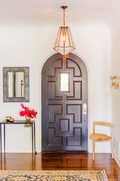 Entryway to feminine and peaceful home with lantern chandelier and bright flowers // front door