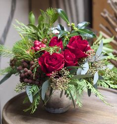 Spreading holiday cheer with vibrant reds and aromatic foliages. Red intuition roses, holly, berzillia, curly pine, cedar and eucalyptus.  http://rogersgardens.com/floral-studio/