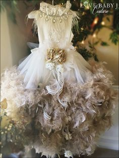 """From the exquisite fabrics used, to the laborious craftsmanship employed, """"Gilded Lily"""" has been lavished with the upmost attention to detail. Available with the feather color of your choice... This dress is PERFECT for weddings!"""
