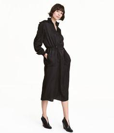 Sort. Kjole i bomuldsblandet satin. Kjolen er i en lige model med opretstående ribkrave og lynlås foroven. Lange ærmer med dobbeltflæser og ribkant. Snøre i