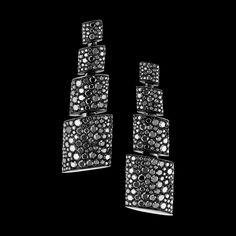 TUBETTO - 2013 - Black rhodium plated white gold - black diamonds - Le reflet de l'esthétique et de l'audace architecturales de de GRISOGONO. L'excitation procurée par la dualité de silhouettes nettes, graphiques, épurées, contrastant avec le mouvement sensuel et enveloppant des courbes et des surfaces planes recouvertes d'une profusion de gemmes, s'enroulant autour de bagues et de boucles d'oreille.