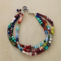 """SPREAD THE JOY BRACELET--A joyous panoply of semiprecious stones including lapis, garnet, red and olive jade, aventurine turquoise, apatite and blue quartz. Three strands meet at the sterling silver lobster clasp. Ours exclusively, handcrafted in USA. 7-3/4""""L."""
