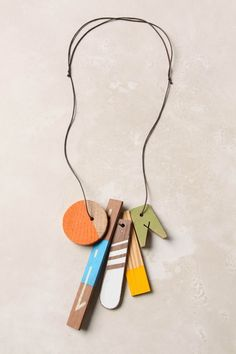 """Merit Badge Necklace      1 review Write a review  We're sorry. This product is no longer available.  DETAILS  Five painted wood pendants signify your aptitude for arts, crafts and style.  Tie closure  Waxed cotton cord, hard wood  34""""L  5.75"""" pendant  Handmade in USA"""