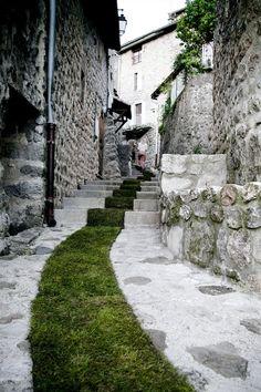 Dans le village de Jaujac en Ardèche, la plasticienne marseillaise Gaëlle Villedary a réalisé «Tapis Rouge», une installation éphémère réalisée à partir de 168 rouleaux de pelouse. Un ruban de gazon de plus de 400 mètres traverse ainsi le village, serpente dans les ruelles, parcours l'espace public, le bitume et le ciment, comme une résurgence du vivant, unfil d'Ariane guidant le promeneur.