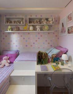 Quarto infantil com papel de parede de bolinhas coloridas.