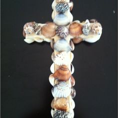 Wooden cross covered with sea shells reminds me he's a fisher of men