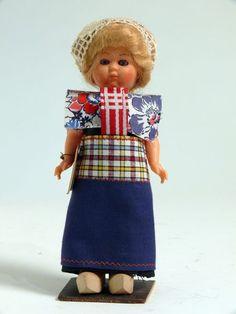 Eine blonde Frau in der Tracht von Spakenburg, Holland. Ein schwarzes Kleid mit karrierten Ärmeln und einer langen blauen Halbschürze mit ebenfalls karriertem breitem Bund. Um die Schultern ein Kragen aus blau-weiß-rot geblümtem Stoff. Vom Schürzenbund ausgehend zwei rot-weiß gestreifte Stoffstreifen vor der Brust und am Rücken. Die Firgur trägt eine Häkelmütze und Holzschuhe. #Spakenburg #Utrecht