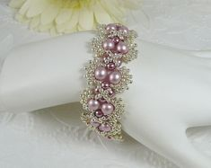 This spiral bracelet uses Swarovski crystals in Amethyst and Light Amethyst with cream crystal pearls securely hand woven with antiqued copper seed beads. The length is 7-1/4 with an antiqued rose box clasp.    https://www.etsy.com/shop/IndulgedGirl