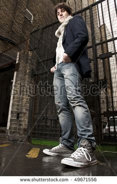 Low angle portrait of young man looking down with gate in the background.