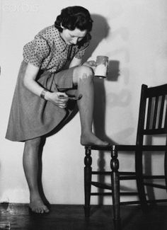 Saving ration coupons for stockings during World War II, a woman in the United Kingdom paints her legs with dark paint so that it appears as though she is wearing stockings.