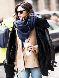 A denim shirt is worn with a camel blazer, shearling moto jacket, blue scarf, and jeans