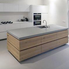 Eikenhout rondom de keuken. Met een betonlook vloer en betonlook werkblad. De opstelling tegen de wand blijft neutraal in mat wit Arpa Fenix. Ook een keuken op maat laten maken? www.houtmerk.nl