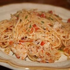 Angel Hair Pasta With Crab Recipe with angel hair, butter, extra-virgin olive oil, sliced green onions, garlic, roma tomatoes, fresh basil, old bay seasoning, salt, pepper, cajun seasoning, chicken broth, lump crab meat, chopped parsley, fresh lemon, grated parmesan cheese