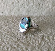 Vintage ring by Avon, introduced in 1977. Size 5 - 6.5, with spacer for adjustable fit.  Oval abalone shell in shades of turquoise blue, green, and iridescent white. Satin silvertone setting with textured rim.   Excellent condition - like new. No scratches, chips, or discoloration. This ring looks unworn.  Clean, bright, and ready to wear.   Bought originally in Maine and owned by the same family for 40 years.    Shop with confidence! I will combine shipping, and I do accept returns.  This…