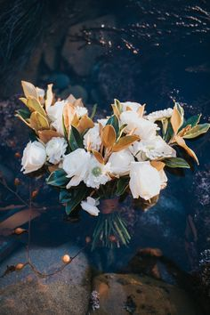 White Rose and Magnolia leaf bridal bouquet with seaweed mixed in. Perfect for a beach wedding or mermaid siren inspired wedding. Stunning image of bouquet floating in the ocean at Sunset Cliffs, San Diego. Wedding inspiration, wedding florals, wedding bouquet, San Diego Florist.
