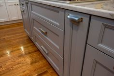 Gray island with silver pulls and granite countertops