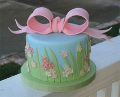Single tier fondant covered cake with fondant decorations and  gumpaste bow.
