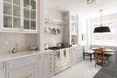 Charming French kitchen boasts a La Cornue Albertine ivory with polished brass hardware placed under a polished nickel pot rack mounted on a gray marble backsplash matching gray marble countertops sat on gray shaker cabinets fitted polished brass pulls.