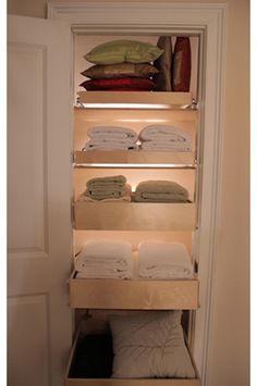 pull out shallow drawers set on tracks allow for easy access to linens stored in the back. Under-shelf lighting is another clever idea