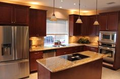 Granite top on surface with a nice shade of brown cabinets. Love this kitchen!