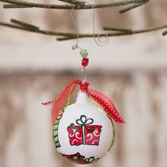 """Ceramic ball ornament with bead and bow accents and a festive motif.  Product: OrnamentConstruction Material: Ceramic, beads, wire and ribbonColor: Red and whiteFeatures: Great addition to any holiday decorDimensions: 4.5"""" DiameterNote:  Additional image depicts back of the ornamentsCleaning and Care: Wipe with clean, dry cloth"""