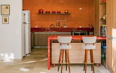 A cozinha do projeto do escritório Arkitito é praticamente monocromática, com ladrilho hidráulico, bancadas e panelas laranjas