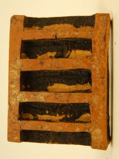 Adinkra-stamp; carved from gourd; stamp shows ladder; six pieces of wood stuck into back of stamp, joined together at opposite end and wrapped in white cotton cloth to make handle.