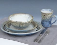 Basic Gammel House Pottery Place Setting Includes:  1 - Dinner Plate, 1 - Toast/Sandwich Plate, 1 - Soup/Cereal Bowl - Choice of Fluted Rim or Flared rim 1 - Bell mug. All of the basics packaged together to get you started. Features: Dishwasher, microwave and oven safe,stackable  Materials: High quality stoneware clay, food safe glazes  All dinnerware is made to order and will take 6 to 8 weeks for Delivery. We like to fire the set all together ensuring the best match possible. We can do…