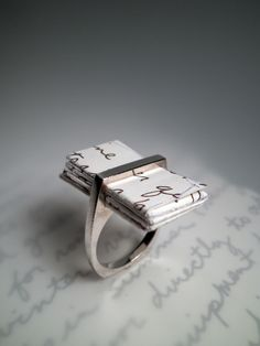 love letter in a ring.  interesting gift for a writer or poet. use metal for the letter..