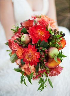 Lovely mixed bouquet of dahlias, calla lilies, and roses in shades of red-orange, peach, and coral with a few apples, hypericum berries, and raspberries for good measure.