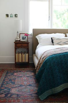Cool rug and pretty dark turquoise bedspread.