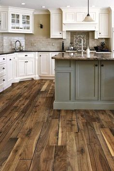 Moving into the kitchen, Pinners all want a rustic wood floor and large center island. We love that this one is a different color than the surrounding white cabinets to make it pop.