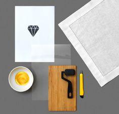 Una tabla de cortar de madera, un cúter, pintura dorada en un bol blanco, un trozo de papel con un diamante dibujado, una servilleta blanca, un rodillo negro de pintura y una hoja A4 de transparencia sobre una superficie gris.