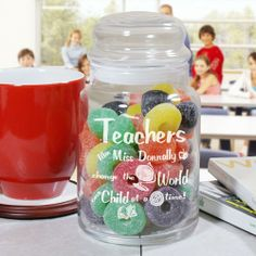 """Engraved Teacher Glass Treat Goodies Jar. Give your favorite teacher a lovely, personalized teacher gift which will look great in the classroom or at home. Our Personalized Teacher Treat Jar is perfect for storing classroom rewards including stickers, candy or little play toys. Your Engraved Teacher Candy Jar measures 5.5""""H x 4""""W and holds 26 oz. Each glass jar comes with an air-tight glass lid. Contents displayed in glass jar not included. Includes FREE Engraving."""